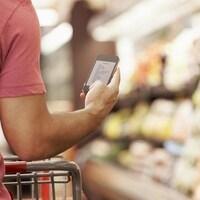 Un homme consulte sa liste d'épicerie sur son cellulaire alors qu'il marche dans un supermarché.