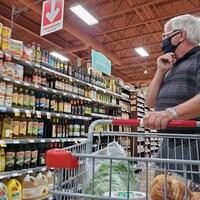 Un homme portant un masque fait ses emplettes.