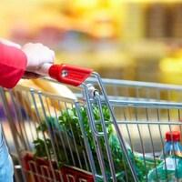 Femme poussant un panier d'épicerie rempli de denrées.