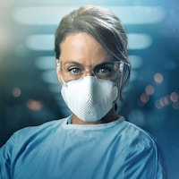 Une femme porte un sarrau, un masque et des lunettes de protection.