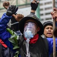 Des manifestants marchent dans la rue, dont un qui porte un masque à gaz.