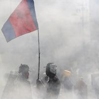 Un manifestant, vêtu d'un masque de Guy Fawkes, dans une rue de Quito obscurcie par les fumées lacrymogènes.