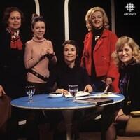 Dans un studio de télévision, Yvette Pard et Francine Bordeleau, Françoise Faucher, Madeleine Gobeil et Aline Desjardins sont rassemblées autour d'une table sur laquelle reposent documents, cendrier et verres d'eau.