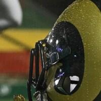 Un casque de footbal doré et vert vu de près avec un arrière-plan flou qui ressemble à un terrain de football.