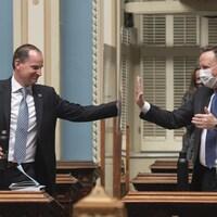 Eric Girard et François Legault posent une main sur un panneau de plexiglas, comme pour se donner une tape de félicitations.