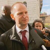 Le ministre des Finances Éric Girard face aux micros des journalistes.