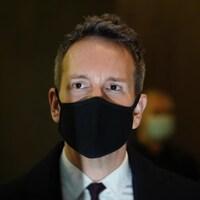 Gros plan d'Éric Salvail qui porte un masque noir.