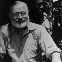 Assis, Ernest Hemingway sourit. Derière, on distingue un homme noir vêtu d'un chapeau.