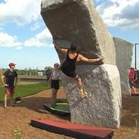 Un grimpeur pratique l'escalade de bloc sur l'esplanade du stade olympique de Montréal.