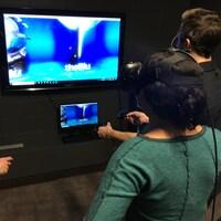 Une femme a un casque de réalité virtuelle sur les yeux, pendant qu'un homme contrôle un ordinateur avec des manettes.