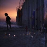 Un enfant se tient près d'un mur séparant les États-Unis du Mexique, au pied duquel des croix et des bougies ont été placées.