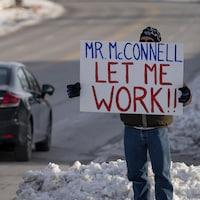 Un homme tient une affiche devant les bureaux du sénateur américain Mitch McConnell, à Park Hills, dans le Kentucky, le mardi 22 janvier 2019.
