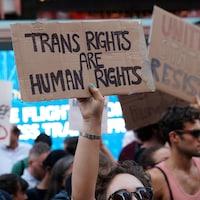 Une personne brandit une pancarte où il est écrit que « les droits des transgenres sont des droits de la personne ».