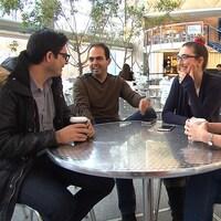 Quatre jeunes discutent autour d'une table dans ce qui semble être une cafétéria.