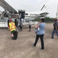 Des personnes s'apprêtent à monter à bord d'un petit avion