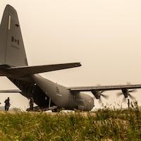 Des gens montent à bord d'un avion Hercules.