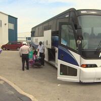 Des passagers s'apprêtent à monter dans un bus.
