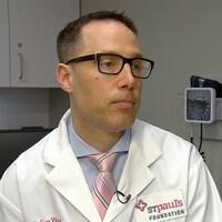 Un homme en sarreau blanc dans un bureau de médecin.