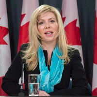 Le portrait d'une femme devant des drapeaux canadiens