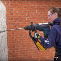 Une jeune femme perce un mur de béton à l'aide d'un appareil installé sur son exosquelette.
