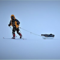 Trois hommes en ski de fond dans une tempête de neige.