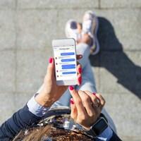 Vue en plongée sur l'écran d'un cellulaire utilisée par une femme qui montre une application de messagerie.