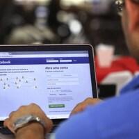 Un homme au clavier d'un ordinateur se branche sur le réseau social Facebook.