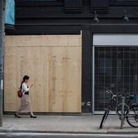 Une femme passe devant la façade d'un commerce placardé.