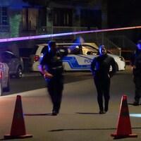 Des policiers passent sous un ruban de sécurité sur les lieux de la fusillade, dans Saint-Léonard.