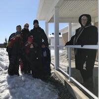 Une femme de 94 ans, avec son manteau noir, est accoudée sur la rampe de sa galerie. Non loin, sa petite-fille et cinq de ses arrière-petits-enfants.