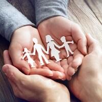 Un homme et une femme se tiennent les mains, dans lesquelles se trouvent des figurines en papier représentant les membres d'une famille.