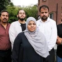 Une famille de cinq personnes : 4 hommes derrière et une femme voilée devant