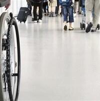 Une personne circule à fauteuil roulant parmi des gens qui n'en ont pas besoin pour se déplacer.