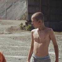 Deux jeunes garçons jouent dans une mine à ciel ouvert.