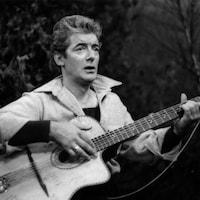 Félix Leclerc, chantant, s'accompagnant de sa guitare.