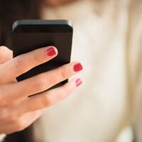 Une femme tient dans une main un téléphone cellulaire. Son visage est hors du champ de l'image.
