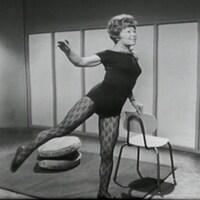 Femme en tenue d'exercice qui fait des mouvements, appuyée sur une chaise.