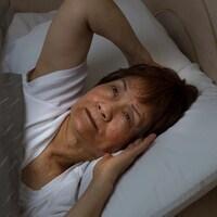 Une femme éveillée dans un lit.