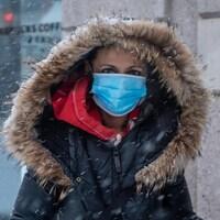 Une femme portant un masque sous la neige passe devant un café Starbucks le 26 janvier 2021.