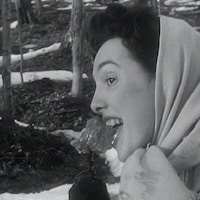 Femme, de profil, qui mange un gros morceau de tire d'érable sur un bâton.