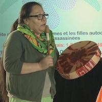 Une femme autochtone joue du tambour traditionnel