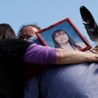 Quatre personnes se serrent dans les bras en portant la photo d'une femme.