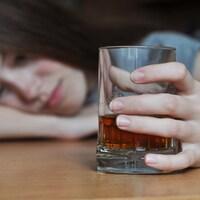 Une femme tient un verre d'alcool à la main, la tête posée sur la table.