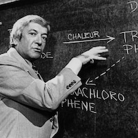 Fernand Seguin devant un tableau qui explique un phénomène scientifique.