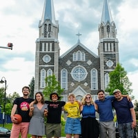 Sept personnes souriantes devant une église