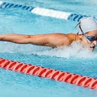 Une nageuse nage le papillon.