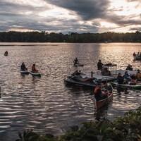 Des personnes sont sur des embarcations sur l'eau.