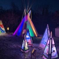 Un tipi et des oeuvres autochtones éclairés.