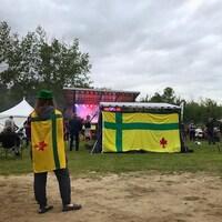 Un festivalier arborant le drapeau fransaskois sur le site du festival.