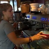 La jeune dame aux cheveux blonds tient un bol devant la machine à café.